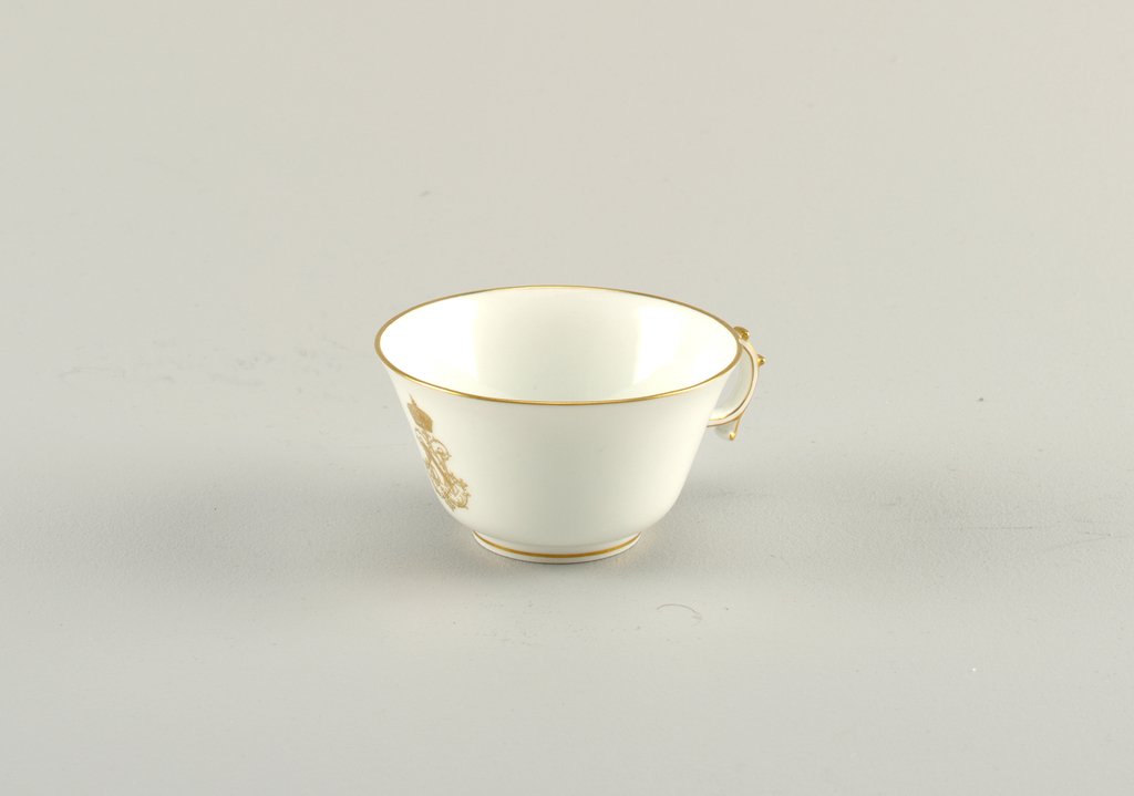 Napoleon III shallow cup with flaring edges. Circular handle with knobs. Flat saucer with curved edges. Gilding on all edges and crowned cipher on cup.