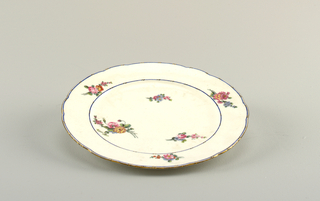 Circular, the rims scalloped and gilt.  Cavetto and border with small polychrome floral sprays on white ground; the border edged with narrow-blue stripes interrupted by short diagonal strokes of gold, in pairs.  Glazed hole in foot ring.