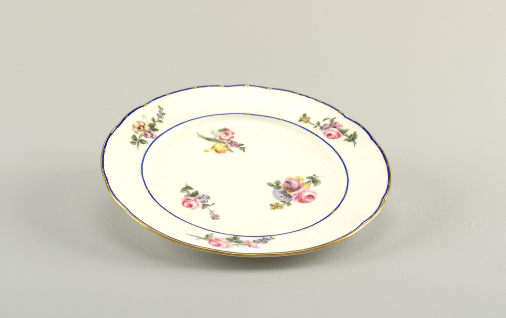 Circular, the rim scalloped and gilded. Cavetto and border with small polychrome floral sprays on white ground; the border with narrow blue stripes interrupted by short diagonal strokes of gold, in pairs.