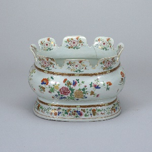 Oval, with bulbous sides and scalloped rim. High foot. Heavy porcelain with pale bluish glaze and floral decoration in five-color enamels, heightened with gold.