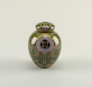 One of a pair; round vase with slightly pointed cover. Decorated with violet and yellow-gold calla lily viewed from above, green vines and leaves surrounding, on brown ground.