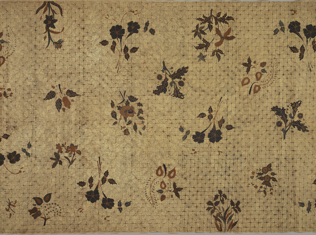 """Long sarong (kain panjang) printed with an all-over pattern of sparsely used flower and leaf designs in white-dotted indigo blue and brown on a light tan ground, which is evenly divided into small all-over geometric pattern of diagonally striped squares (""""isen"""" motif)."""