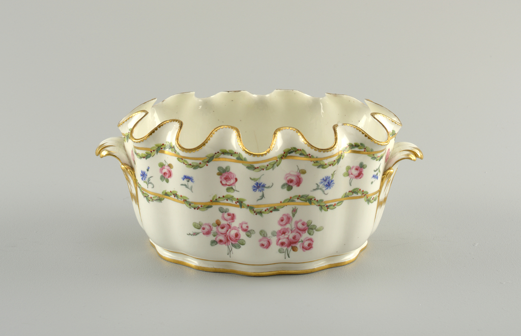 Oval, with wavy sides and incurving scalloped edge. Curved foliate handle at either end. Decorated with horizontal gold bands twined about with laurel cables, and scattered roses and bunches of roses.