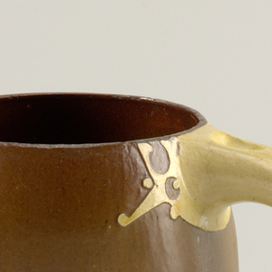 Brown jug with curved handle in yellow; and rounded geometric decoration at seams of handle, like open-mouthed creatures. Under spout, abstract mask with curled ears.