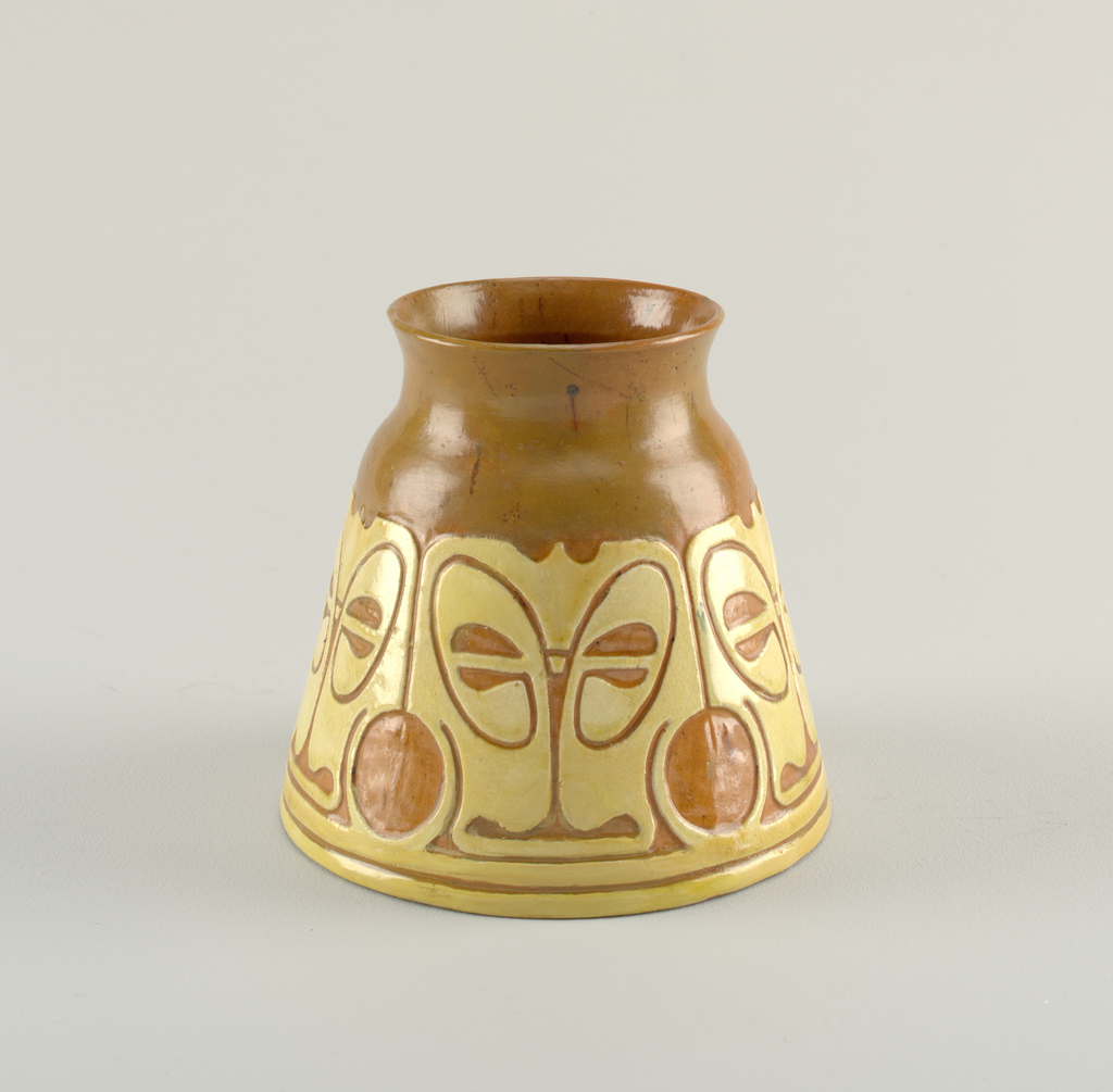 A conical vase with a repeating abstract pattern in colored slip around the body.