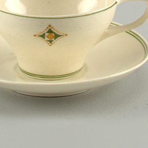 Decorated with green and ochre four-pointed geometric star and linear bands on cream ground.
