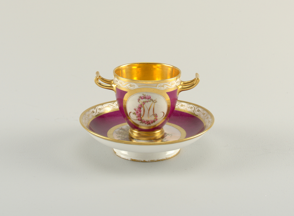 Cup with a gilded, receding foot. Two gilded, horizontal handles in the antique style. Decorated with a purple, gilt borders and two circular reserves with the monogram MC, the latter letter in the form of a garland of roses. Saucer has a tall foot and high sides.