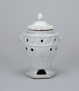 Vase=shaped stove on a hexagonal base. Lion-head antefixes. Relief molded decorated of guilloche below rim and vertical leaves above base. Pierced holes. Domed lid with finial.