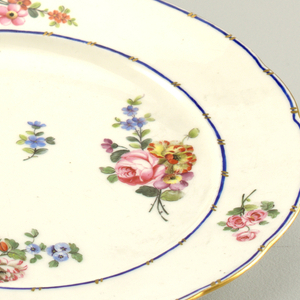 Circular, the rim scalloped and gilt.  Cavetto and border with small polychrome floral sprays on white ground; the border edged with narrow blue stripes interruted by short diagonal strokes of gold, in pairs.  Glazed hole in foot ring.