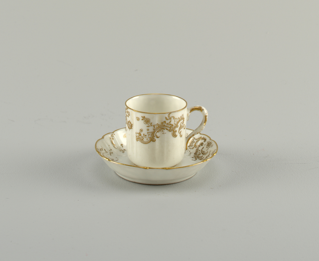 straight demitasse, divided by vertical depressions into six panels; shaped handle. Dish-like saucer, with six wide and six narrow lobes. Stamped overglaze gold scrolls and flowers, gold edges. Marked up on cup and saucer.