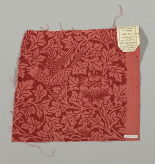 Design of flowering branches and perched birds, in pink on a red ground.