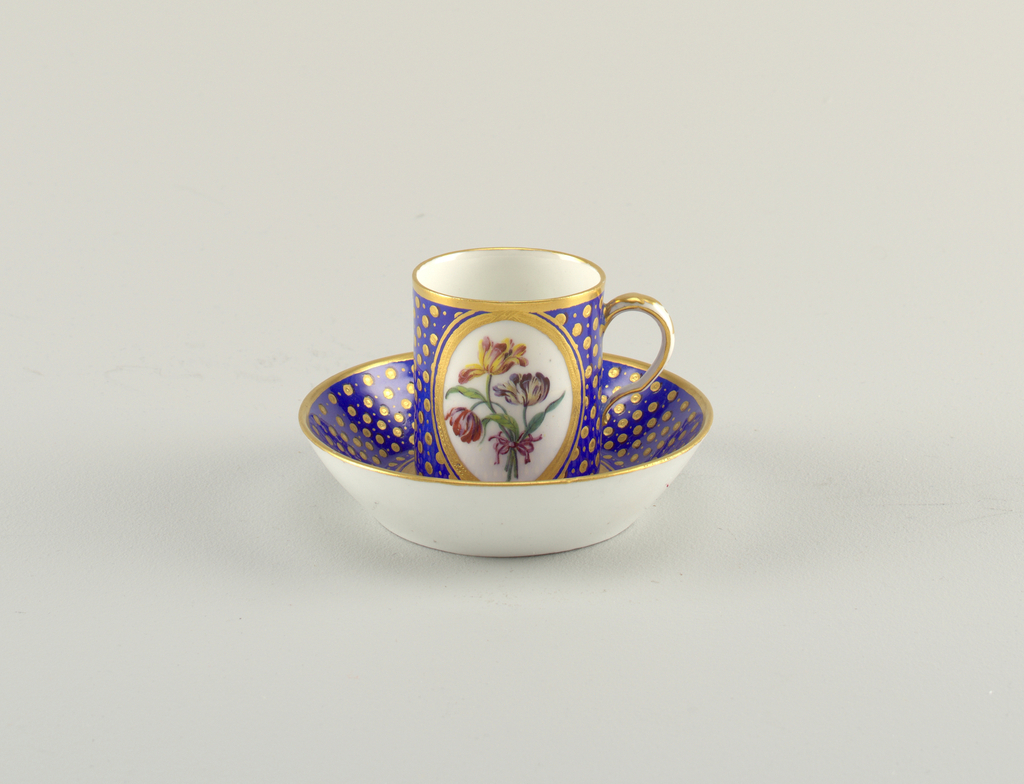 Short, cylindrical cup (a) with scroll handle; enamel and gilded decoration consisting of gilt dots picked out in black, on blue ground; large, central, gilt-bordered oval cartouch with spray of three tulip blooms (red/cream, yellow/red, purple/cream) tied with pink ribbon; narrow gilt bands at mouth and base. Saucer (b) with everted rim decorated en suite with cup, the circular well with spray of vari-colored, petalled flowers tied with yellow ribbon.
