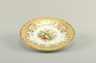 Flat marli and smooth rim. At center, white ground with overglaze florals. Surrounding this, a beige grown with gilt scrollwork.