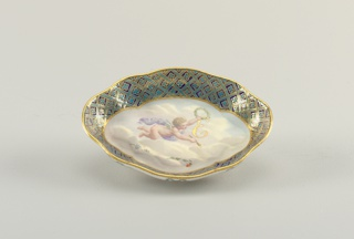 Oval dish with broadly scalloped edge. Wide rim painted with quatrefoil and lattice pattern. At center, a flying putto with laurel wreath and the gilded letter E.