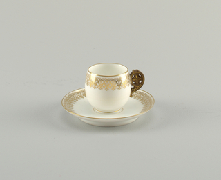 Curved demitasse of white porcelain with gold edges and transfer-printed scrolled band in gold. Wheel-shpaed handle, brown and gold. Saucer with similar gold band.