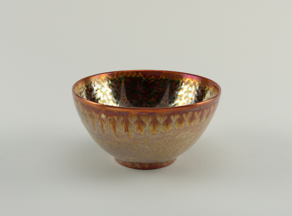 Deep bowl with rosy ground mottled with bold luster on low ring foot; copper red lustered rim above interior deisgn of eight dark green deep scallops patterned with seaweed-like design in copper-red; silvery-gray 8-loved pattern on bottom of bowl interior with copper-red seaweed-like design.