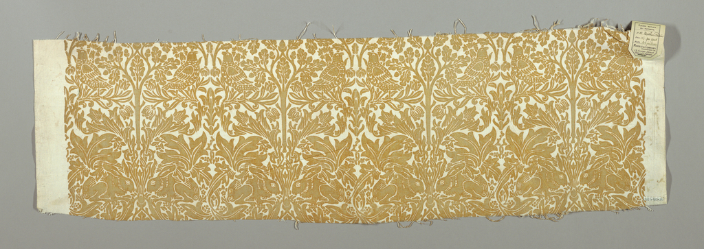 Medium-scale symmetrical design of an oak tree with confronted rabbits at either side of base; confronted birds with floral motif in interstices. Golden tan on white ground. Wide plain unprinted selvedges.