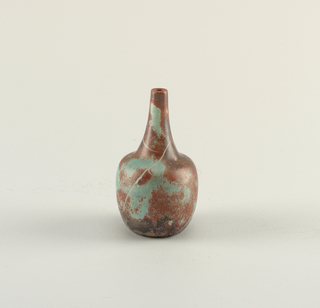 Rounded footless body with tall neck; red, turquoise and dark grey mottled glaze.
