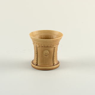 A small brown cup with flower motif stamped on its sides framed by scalloped bands on the body.
