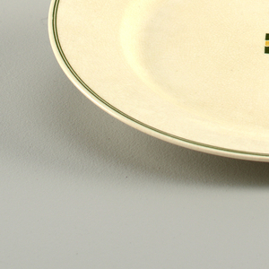 White plate with a thin double lined black border close to the edge of the rim. Small black and yellow checker board pattern in the center.