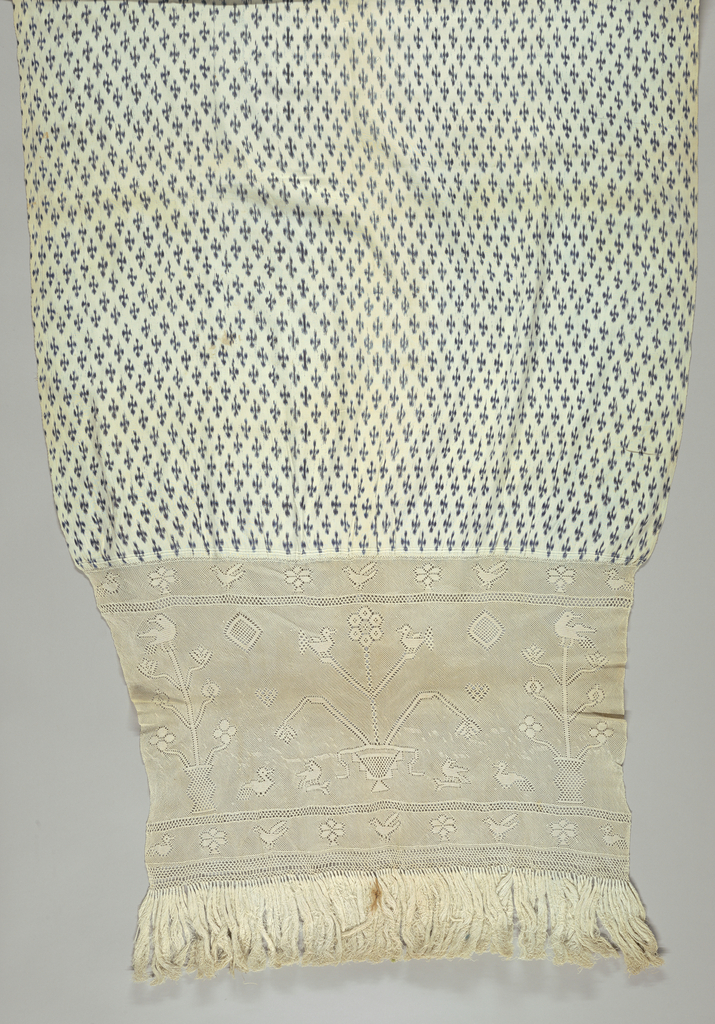 Shawl patterned in an ikat design of a bird motif arranged in rows offset in alternating rows. The undyed warps at each end are knotted to produce an open fabric with a pattern of flowering plants in a pot with a bird perched on top, single birds and flowers – about 17 inches. Ivory cotton fringe about 5 inches long attached to the knotted sections at each end.