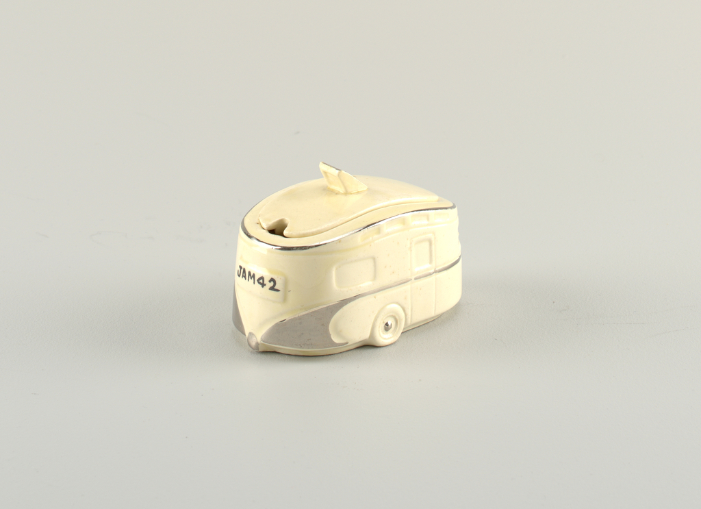 "Jam pot molded in form of a two-wheeled trailer, the cream-colored ground with details picked out in silver-toned glaze and license plate emblazoned with ""JAM 4 2""; the cream-colored oval, slightly domed lid in form of trailer roof with ""vent"" as tab handle; small opening for spoon at rear."