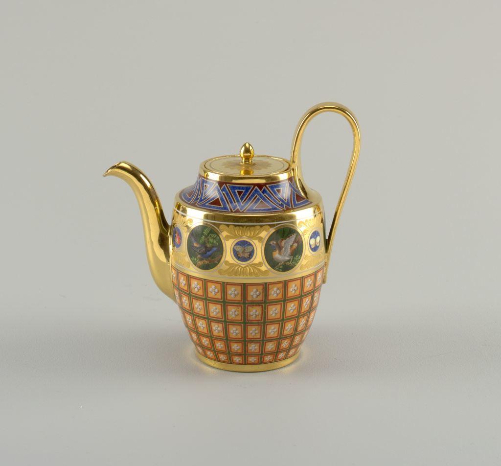 Flat-based teapot with curved sides, tall strap handle and curved spout; flat top with circular cover with acorn finial. Cover, hand and spout gilded. Body decorated with roundels painted in polychrome enamels depicting birds, alternating with smaller roundels with butterflies.