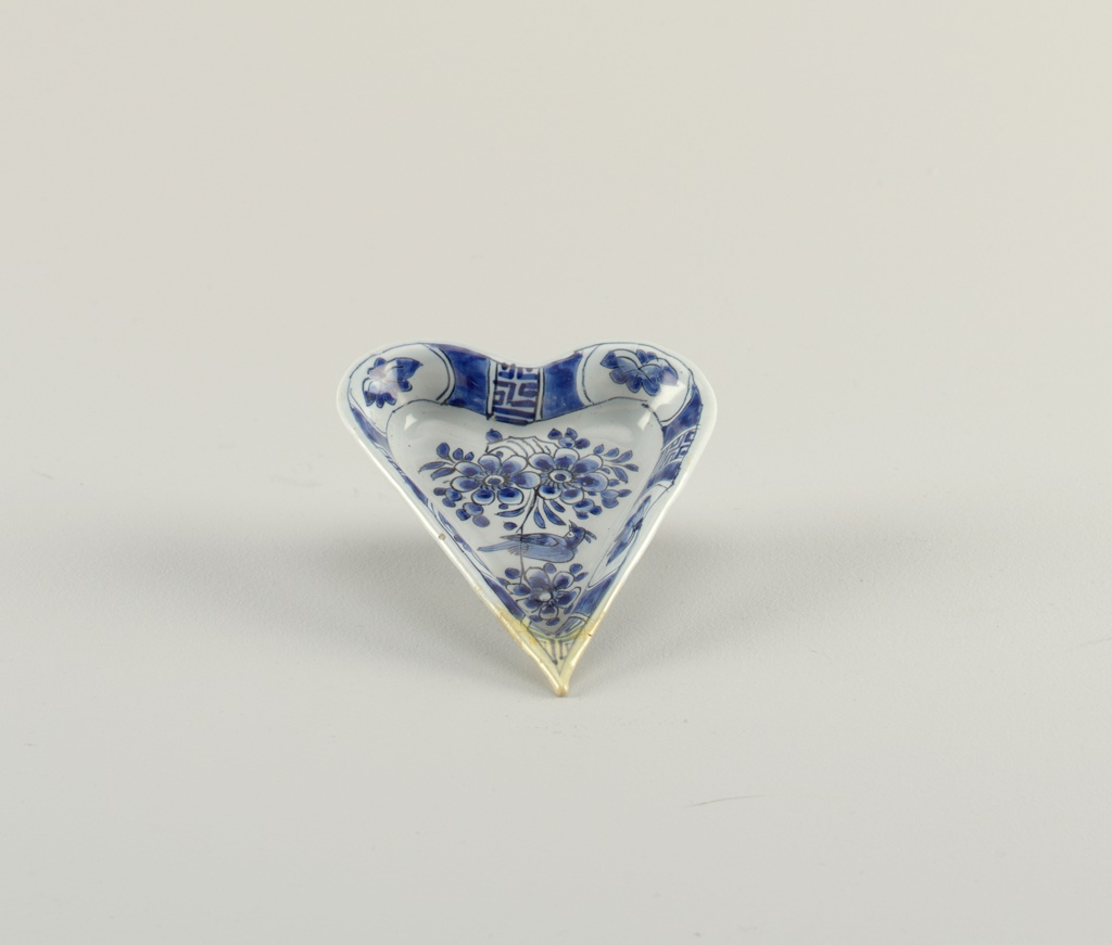 Heart-shaped dish on short foot rim with slightly flared sides; painted in underglaze blue on white with birds and flowers in center, on sides with alternating panels of flowers and pseudo-Chinese characters.