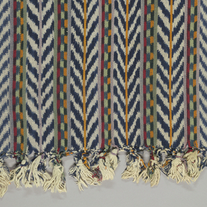 Long narrow striped rebozo with a chevron-patterned stripe in blue and white ikat alternating with a group of three narrow stripes patterned with squares yellow and blue, green and blue, or red and blue ikat. With narrow solid stripes in yellow, purple and green. Two solid blue stripes at either side.
