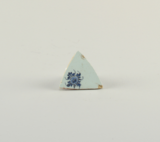 Fragment of a bowl. Pale blue glaze over war, earthenware body. Flowers and foliage painted in cobalt.