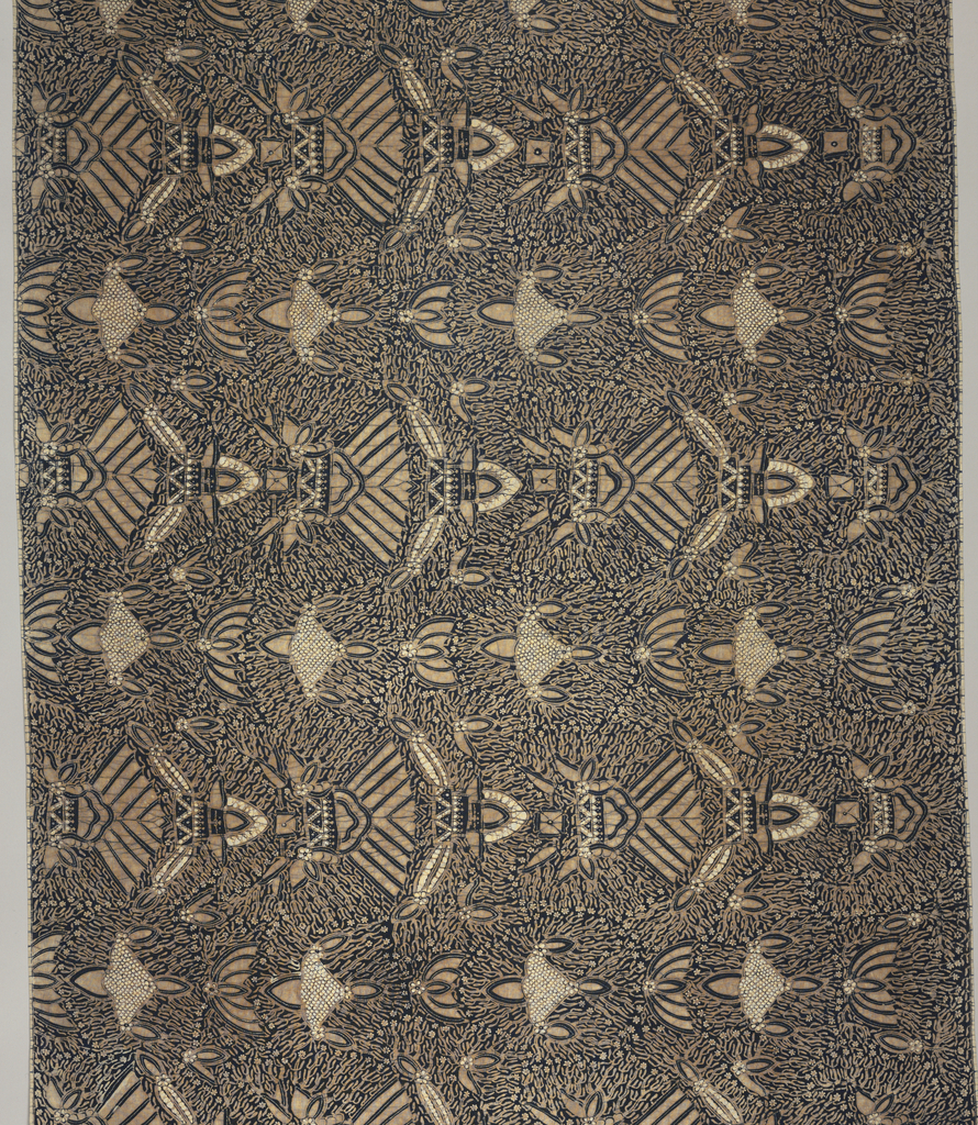 """Long batik sarong (kain panjang) in dark blue, light brown, and white. Dark blue ground showing numerous white dots known as """"gabah sinawur"""" or 'grains of rice'. Also shows an all-over pattern of heraldic motifs """"semen"""" (curling tendrils and other non-geometric forms) and """"sawat"""" (wings and tail of Garuda, mount of Vishnu) as well as mountains ."""