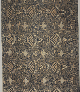"Long batik sarong (kain panjang) in dark blue, light brown, and white. Dark blue ground showing numerous white dots known as ""gabah sinawur"" or 'grains of rice'. Also shows an all-over pattern of heraldic motifs ""semen"" (curling tendrils and other non-geometric forms) and ""sawat"" (wings and tail of Garuda, mount of Vishnu) as well as mountains ."