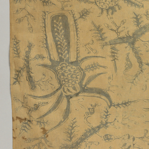 "Yellowed cotton, possibly a long sarong (kain panjang), patterned in blue (faded) by unidentifiable plant forms and border at one end with ""tumpal"" motif (row of isosceles triangles) containing a plant on a vine."