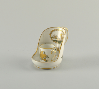 Cylindrical cup with handle. Saucer has one side extended upward to form a windshield, with handle. Decorated in gold and green, with flowers and medallion with landscape.