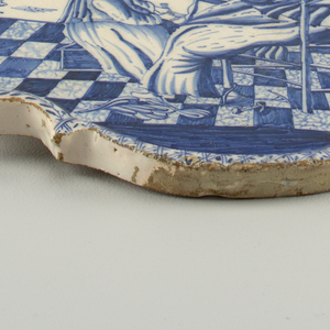 Shaped oval plaque with raised border; painted in underglaze blue on white with domestic scene of woman and child at spinning wheel, diaper and vine border; back unglazed.