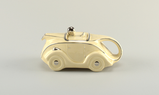 "Teapot in form of roadster with spout at front, D-shaped handle at rear; square lid molded with top of steering wheel and driver's head. The whole in cream-colored ground with details (including grill, headlights, driver's cap and goggles) picked out in sliver-toned glaze. License plate with ""OK.T42"" at front."