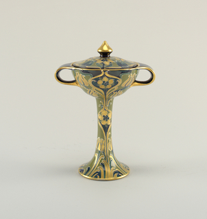 A candy dish with lid similar to a goblet form with a high foot. Handles opposite sides. Decorated with floral pattern of gold on dark background.