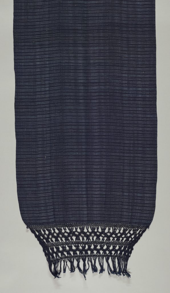 Long narrow rebozo with very fine ivory vertical dash pattern on dark indigo. Warp fringe knotted at both ends.