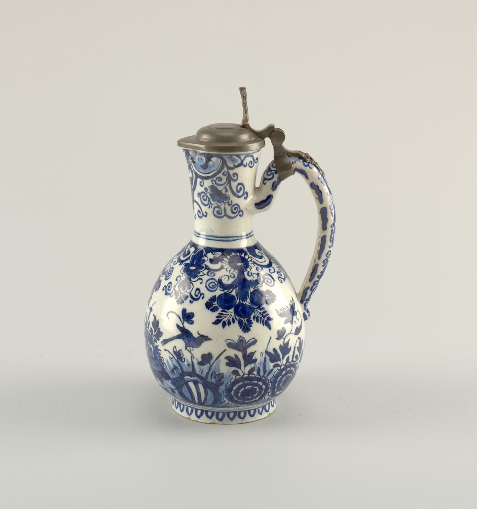 Ovoid body on short foot rim, long neck slightly flared, small everted spout; looped handle; low domed pewter cover, tall thumbpiece with female fish figure attached at handle with trailing cutwork strap; painted in deep blue underglaze on white with chinoiserie birds, flowers, lambrequins.