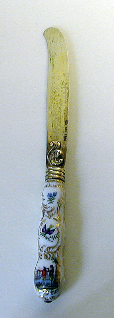 Gilded sabre-shaped blade, bolster decorated with scrolls in relief. Ribbed ferrule, round in section. Tapering white porcelain handle with multi-color decoration of flowers, birds and two scenes: on the front side, two men looking out over a harbor. On the back a lady with a fan standing outside next to a rosebush; landscape with trees.  Gilded, scrolled decoration around scenes, along the sides, and on the top of handle.