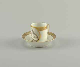 Cylindrical cup with slightly flaring sides and scrolling handle. Flat saucer with flaring rim. Decorated with plain and foliate gold bands. On cup, a grisaille medallion of a woman nursing a winged child. On saucer, a medallion with urns, wreath and drapery.