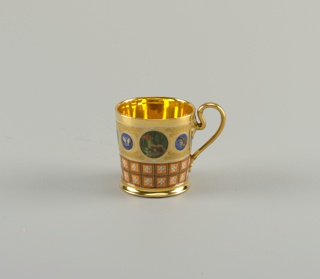 Flat-based cup with straight sides, tapered slightly outward toward lip. Loop handle with rosette at juncture at upper end. Handle and interior completely gilded. Decorated outside en suite with service: three large roundels with birds, four with butterflies.
