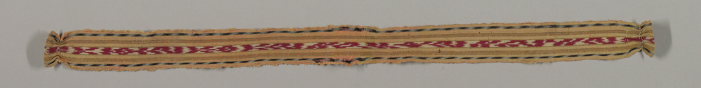 Narrow woven band patterned by stripes: the center and widest stripe is patterned by ikat in red and white. The narrow stripes on each side are orange, red-orange with gold pinstripes on each side and an ikat patterned stripe in blue and white. Each end is turned under and sewn with a narrow salmon tape attached to one end and a strip of green silk to the other.