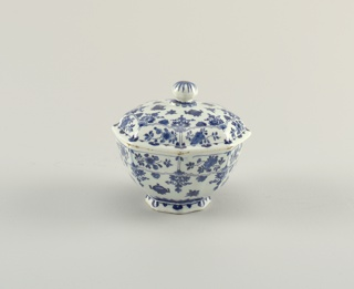 Eight-sided bowl on short foot; domed cover with ball finial; painted in underglaze blue on white, around body with Chinese pots and border of floral reserves, on cover with matching design, on finial with flower.