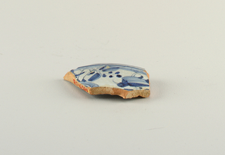 Fragment of pottery with tin and cobalt glaze on surface of earthenware. Decoration shows a bird and plant.