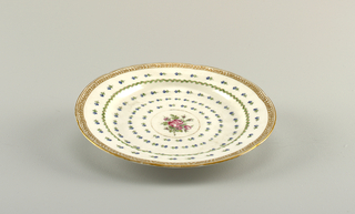 Flat marly, scalloped edge. Overglaze decoration in polychrome and gilding showing six concentric rings of flowers, with cluster of roses in center.