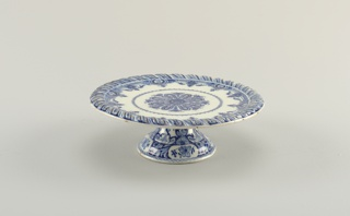 Flat circular top with raised gadrooned border at outer rim, on hollow stemmed domed base; painted in underglaze blue on white, on base with floral reserves on leafy border, on top with central rosette surrounded by scroll, lambrequin, and gadrooned borders, on underside with 4 groups of 4 dots.