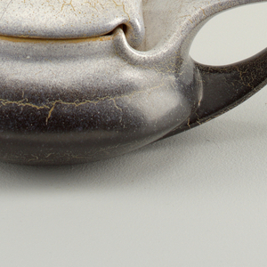 of chamberstick form, with wavy lid, and elongated handle, glazed in shades of white, and grey