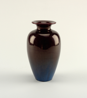 elongated ovoid, footless body, short neck, flaring lip. dark mulberry glaze on lip and upper body shading into deep blue near base over coarse white earthenware body.