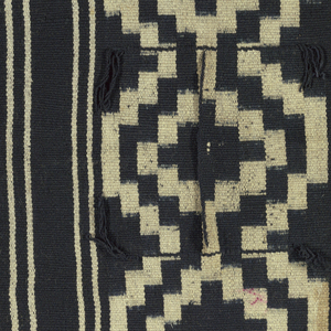 Poncho with neck slit in center patterned by three broad stripes, each with a continuous geometric symmetrical repeat isolated by narrow white stripes.